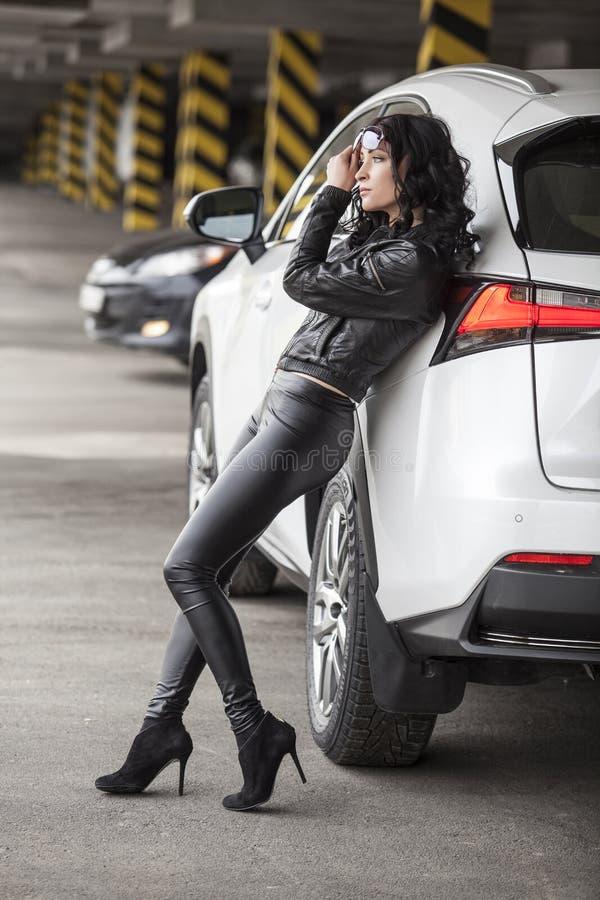 Det härliga kvinnliga modellanseendet på en vit bil i sexigt poserar fotografering för bildbyråer