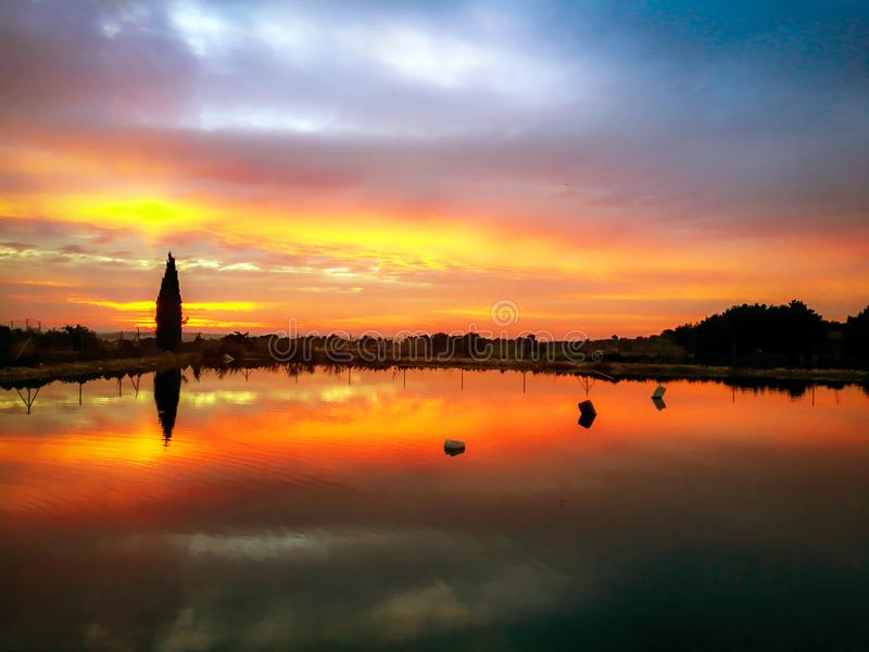Det härliga landskapet av solnedgången reflekterade på en sjö över bergen royaltyfria foton