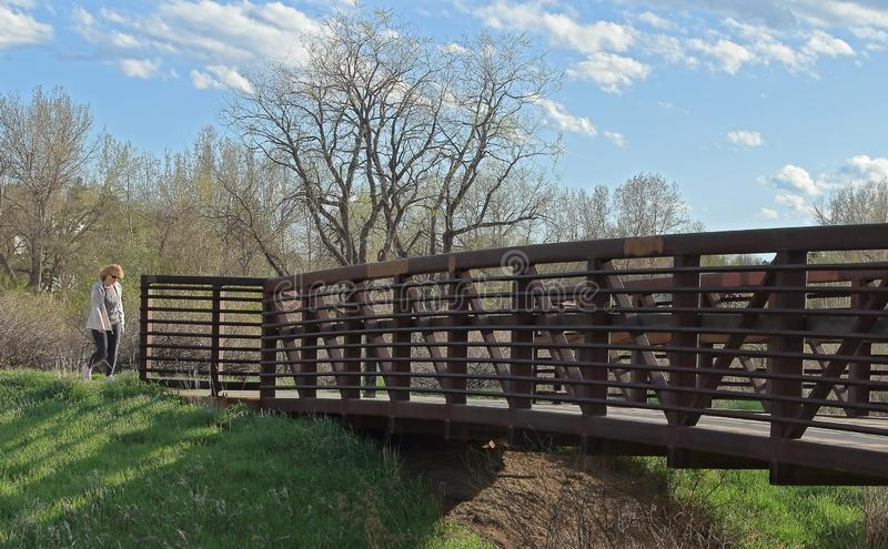 Det härliga landskapet med den fot- bron i den lilla grannskapen parkerar, den lokala kvinnan som kommer till bron arkivbild