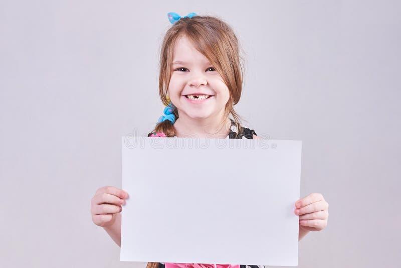 Det härliga liten flickainnehavet räcker in ett vitt ark av papper royaltyfri bild