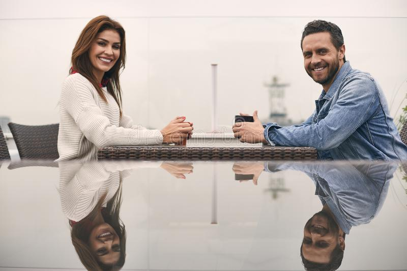 Det härliga paret sitter på kafét tillsammans fotografering för bildbyråer