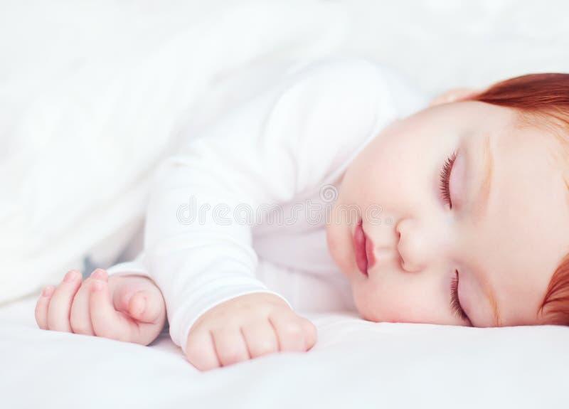 Det härliga rödhårig manspädbarnet behandla som ett barn att sova i säng arkivbilder