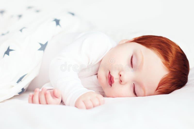 Det härliga rödhårig manspädbarnet behandla som ett barn att sova i säng arkivfoto