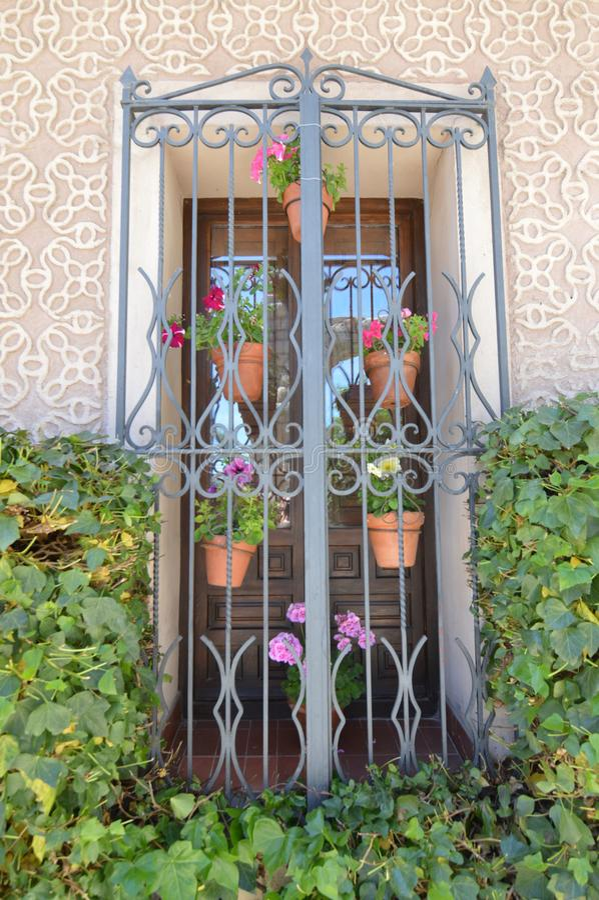 Det härliga typiska fönstret av söderna av Spanien dekorerade med pelargonblomkrukor med en härlig vägg av mosaiker som förbi omg royaltyfri fotografi