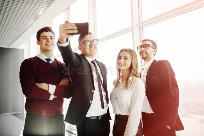 Det härliga unga affärsfolket gör selfie genom att använda en smart telefon och le i regeringsställning rum arkivbilder