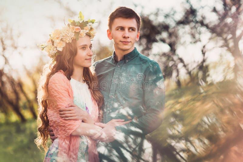 Det härliga unga caucasian paret som har ett romantiskt datum i solnedgång, tänder royaltyfri bild