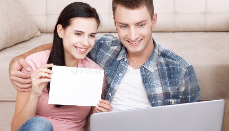 Det härliga unga paret som använder bärbara datorn, meddelar i video pratstund En kvinna är le och visa det tomma stycket av papp arkivbild