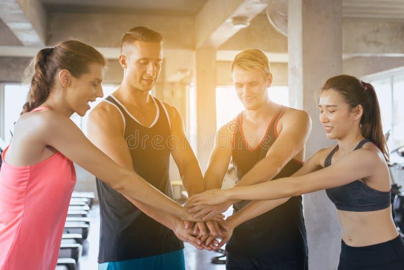 Det hållande sportlaget som är attraktivt och eller, sammanfogar händer tillsammans, handkoordination av motiverat gruppfolk royaltyfri bild