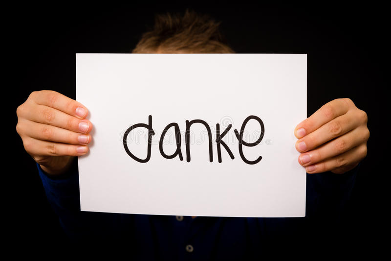 Det hållande tecknet för barnet med det tyska ordet Danke - tacka dig royaltyfria foton