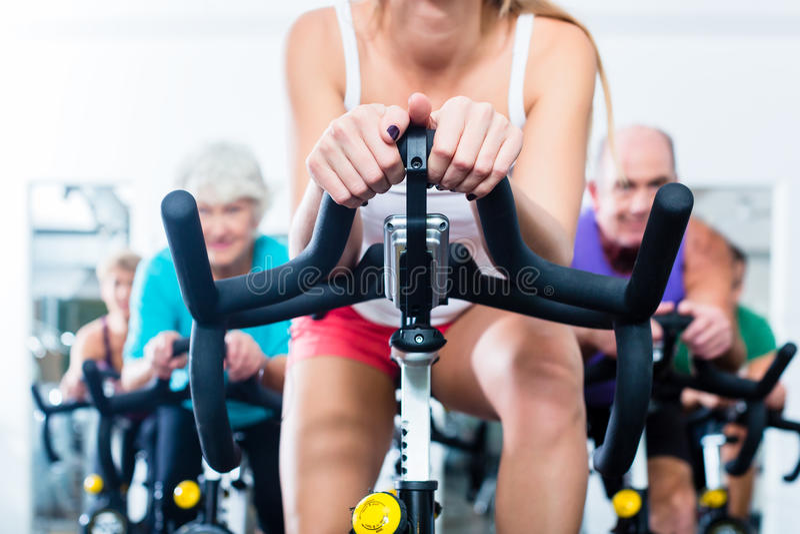 Det höga folket i idrottshallsnurr på kondition cyklar arkivbilder