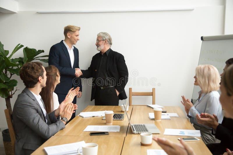 Det höga framstickandet som främjar anställd som skakar händer, team att applådera på royaltyfri fotografi