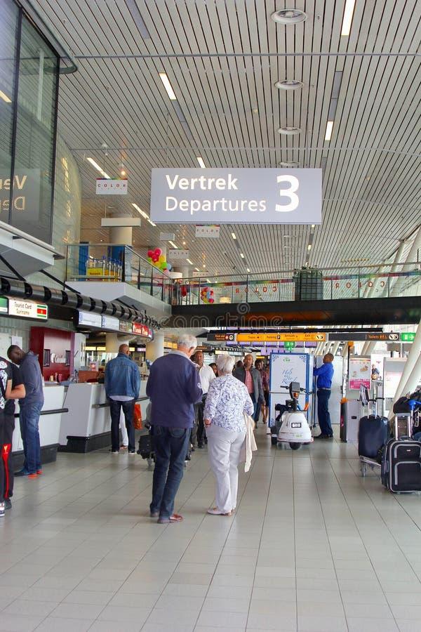 Det höga paret är avtågande från den Amsterdam Schiphol flygplatsen, Nederländerna royaltyfri foto