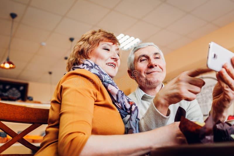 Det höga paret gör en selfie genom att använda en smartphone i kafé Fira årsdag Pensionerat folk som har gyckel fotografering för bildbyråer