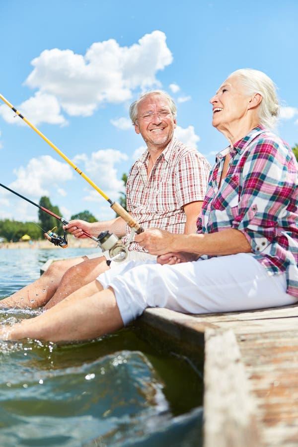 Det höga paret har gyckel som fiskar på sjön arkivbilder