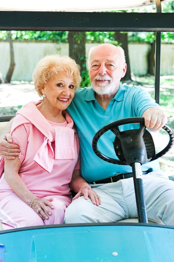 Det höga paret kör golfvagnen royaltyfria foton