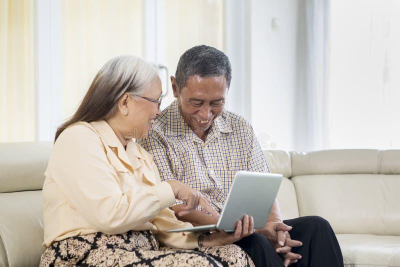 Det höga paret ser lyckligt med bärbara datorn hemma arkivbilder