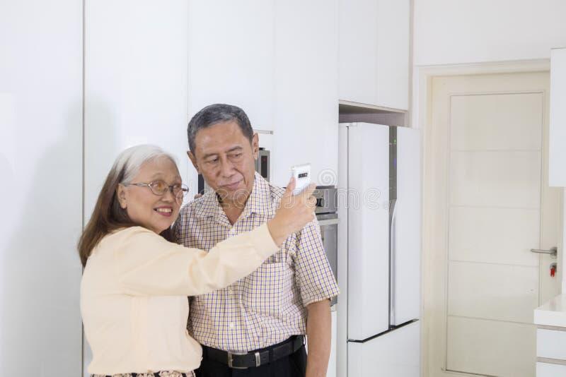 Det höga paret tar ett foto tillsammans i köket arkivbild