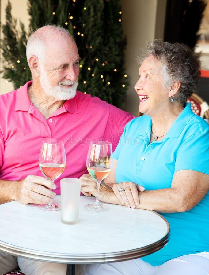 Det höga paret tycker om coctailar royaltyfri bild