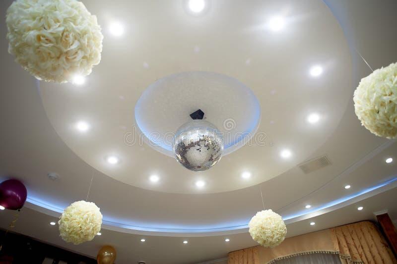 Det höga vita taket med utsatta strålar Dekorerat med diskobollar Med panelljuset livstidsnatt arkivbild