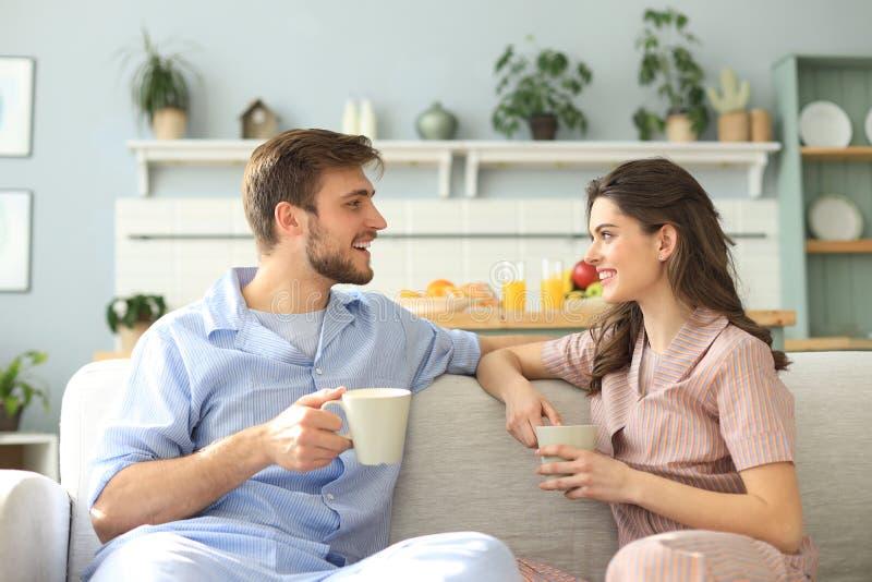 Det h?rliga unga paret i pyjamas ser de och ler p? en soffa i vardagsrummet fotografering för bildbyråer