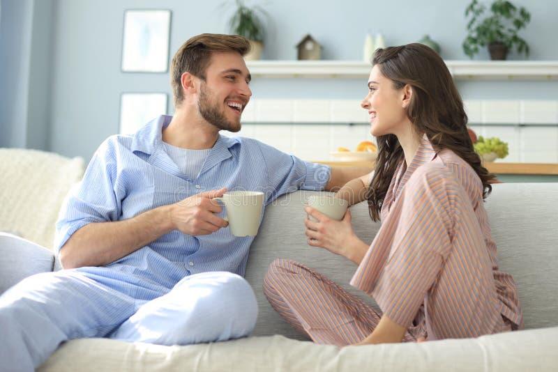 Det h?rliga unga paret i pyjamas ser de och ler p? en soffa i vardagsrummet arkivbild