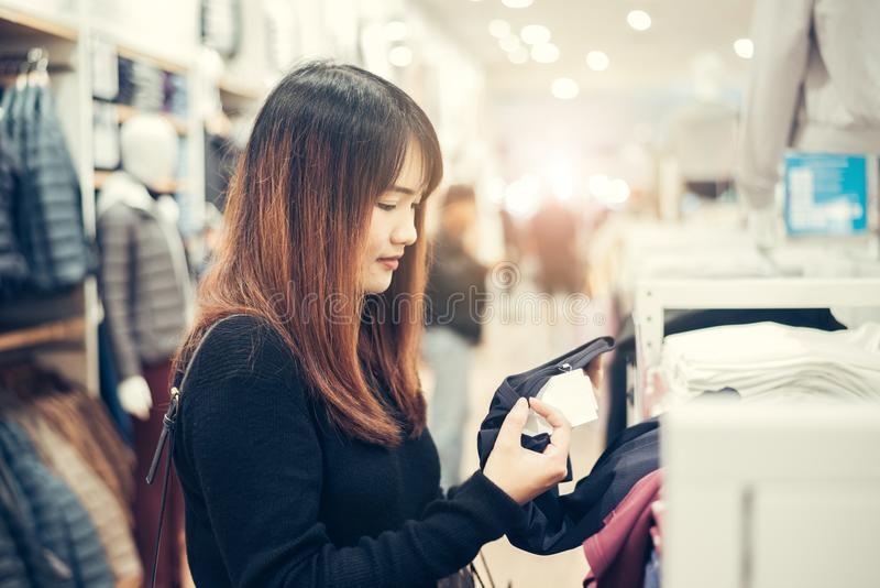 Det halva kroppskottet av en lycklig asiatisk ung kvinna med skuldrapåsen som ser kläder som hänger på stången inom kläderen, sho arkivbilder
