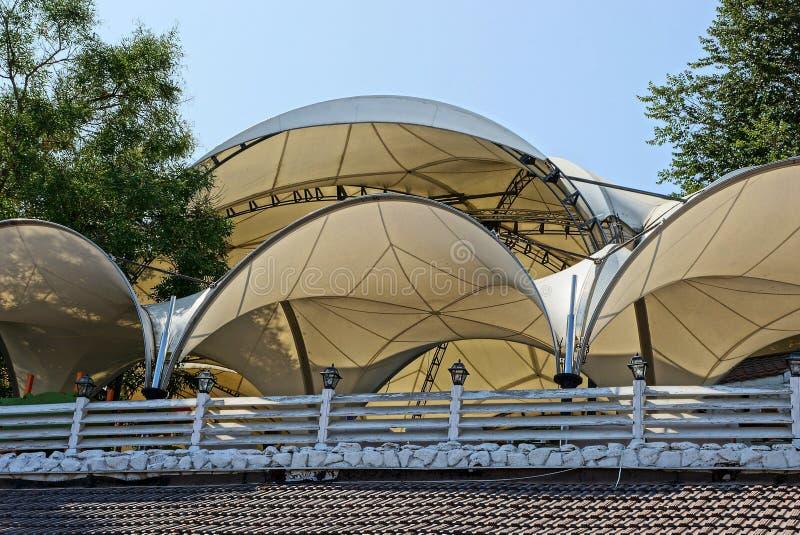 Det halvcirkelformiga bruna taket av tyget av tälten bak staketet arkivbilder