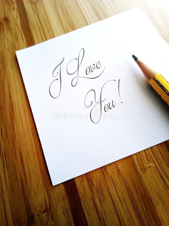 Det handskrivna meddelandet älskar jag dig på vitbokanmärkning arkivbilder
