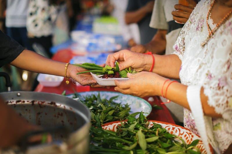 Det hemlösa folket hjälps med matlättnad, svältlättnad: volontärer som ger mat till fattigt folk i desperat behov: Begreppet royaltyfria bilder