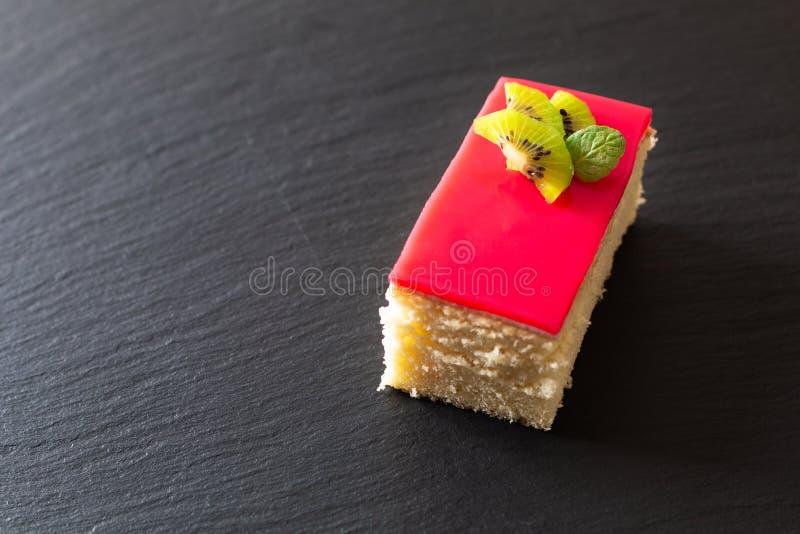 Det hemlagade organiska stycket av sås för bär för vaniljsockerkaka röd på svart kritiserar stenplattan med kopieringsutrymme royaltyfria foton