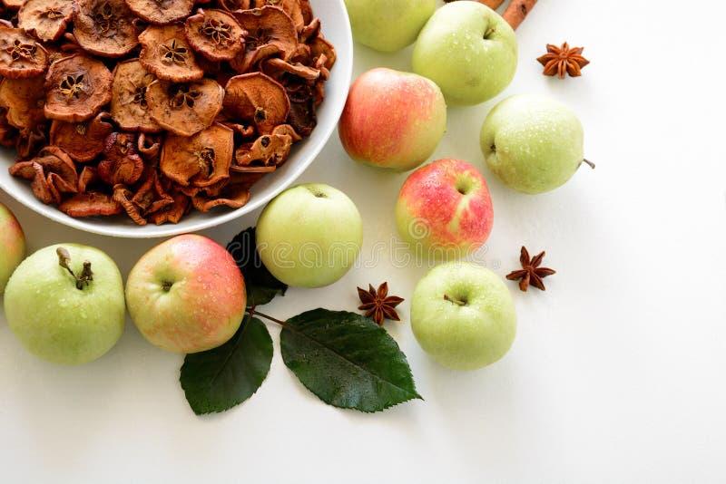 Det hemlagade sol-torkade organiska äpplet skivar frasiga äpplechiper med det ny äpplet och kanel på vit träbakgrund fotografering för bildbyråer