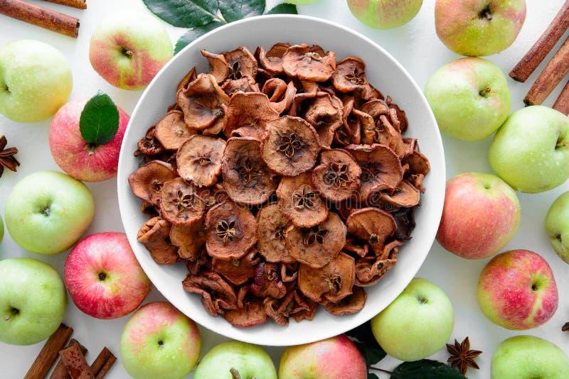 Det hemlagade sol-torkade organiska äpplet skivar frasiga äpplechiper med det ny äpplet och kanel på vit träbakgrund Top beskådar royaltyfri bild