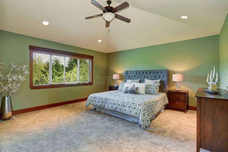 Det hemtrevliga sovrummet med blått bäddar ned, knapphuvudgaveln och gräsplanväggar arkivfoton