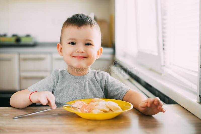 Det hungriga barnet äter ukrainska klimpar i köket som sitter på en stol i en grå t-skjorta royaltyfria foton