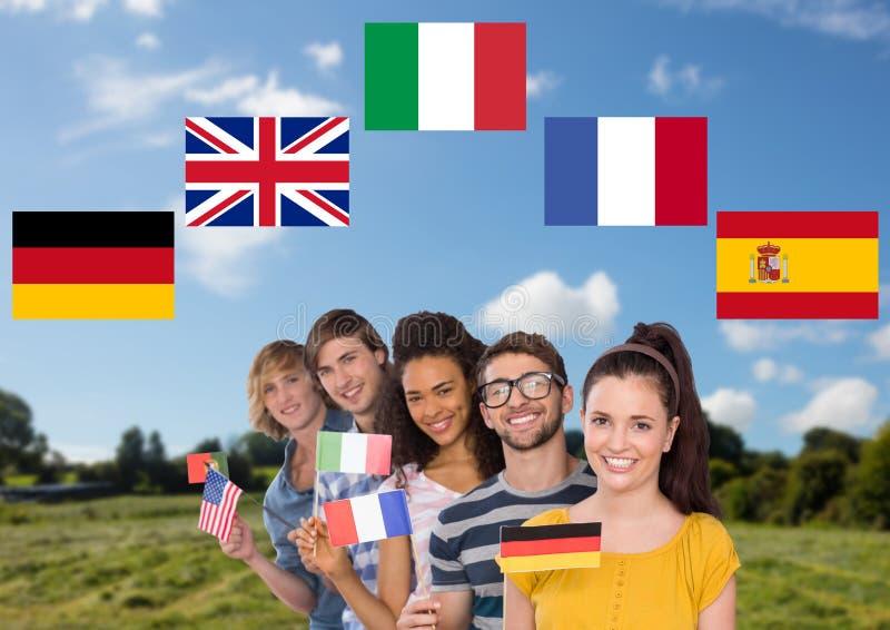 det huvudsakliga språket sjunker runt om grupptonåringar med flaggor i fält royaltyfria foton