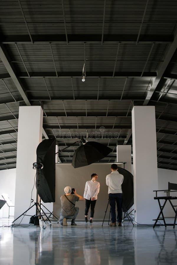 Det idérika fotoet och videoen team skytte i studio fotografering för bildbyråer