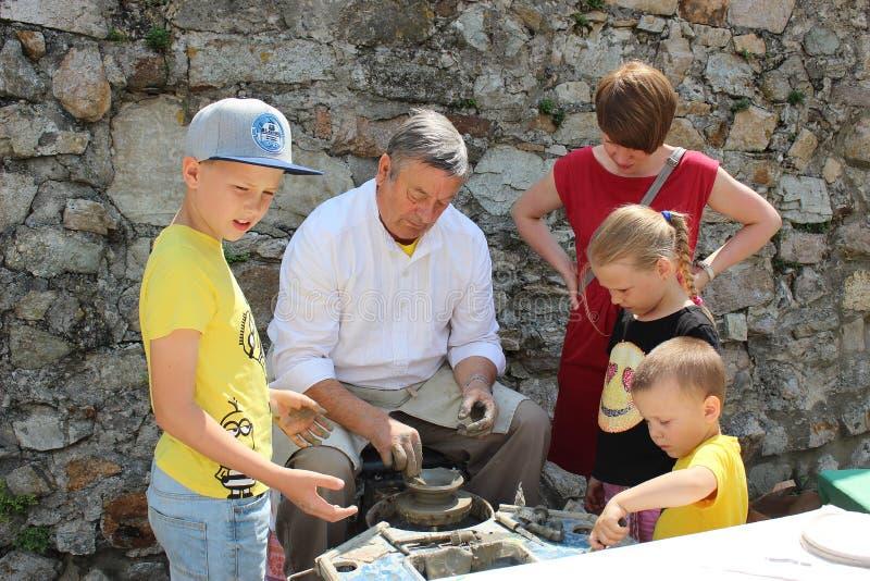 Det idérika seminariet av traditionellt handcrafts - keramikern undervisar barn hur man gör krukmakeri på potterÂs hjul arkivbild