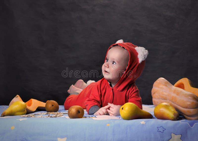 Det Iittle barnet ligger på tabellen med päron och en klippt pumpa royaltyfri fotografi