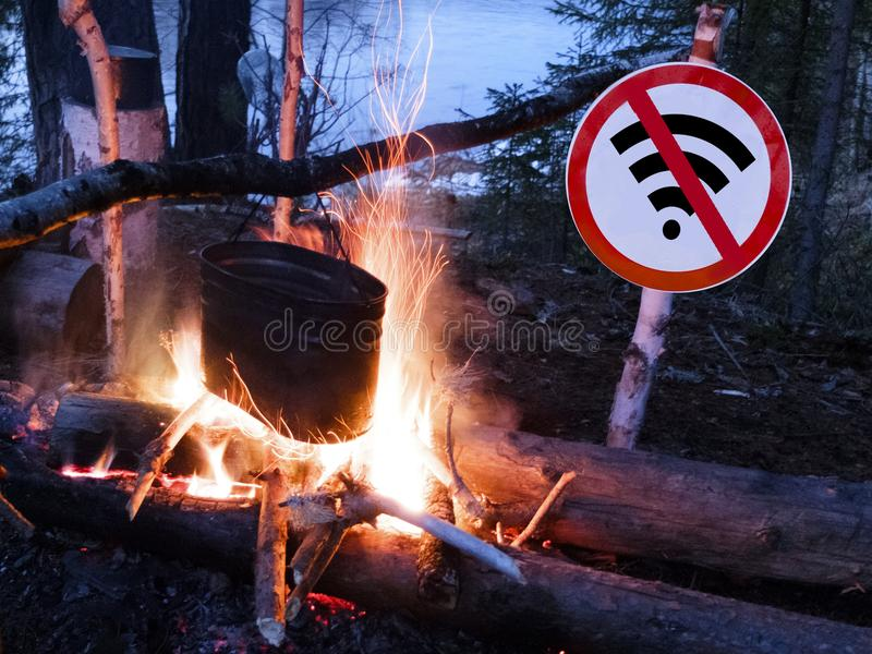 Det inget wifitecknet nära branden och krukan på stranden digitalt detoxbegrepp och avbrott från teknologi royaltyfri bild
