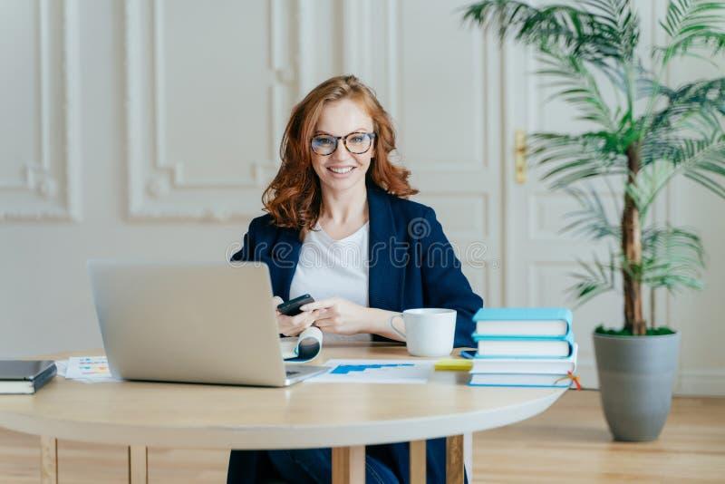 Det inomhus skottet av den röda haired kvinnliga ekonomen överför textmeddelandet till kollegan, rymmer den moderna smarta telefo royaltyfri fotografi