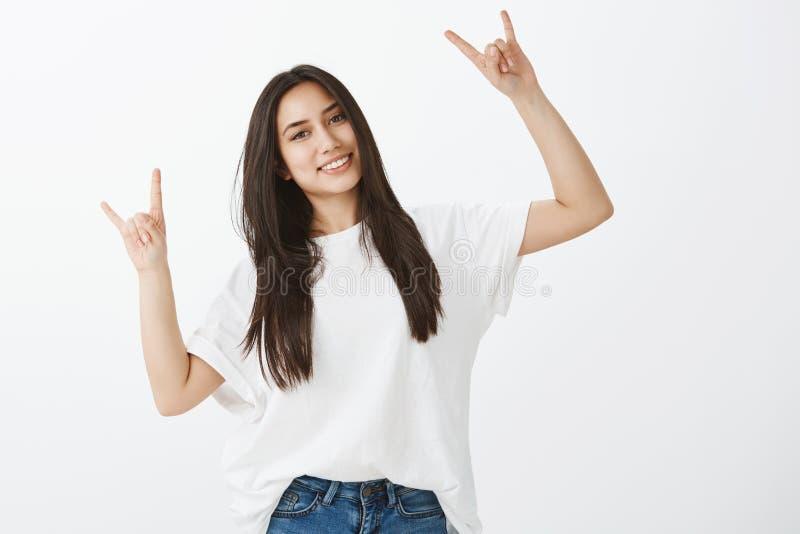 Det inomhus skottet av den snygga vuxna kvinnlign i den vit t-skjortan och jeans som lyfter händer med, vaggar gester och att le arkivbilder