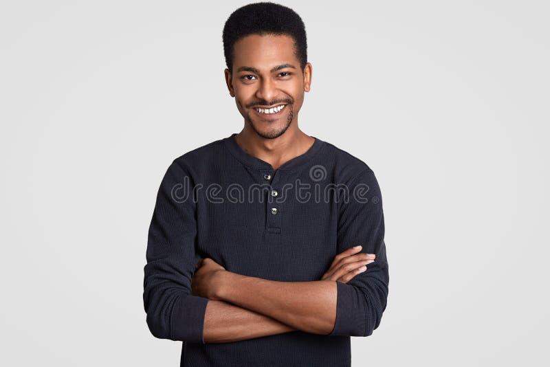 Det inomhus skottet av den stiliga tillfredsställda svarta mannen med vikta armar, bär tillfällig kläder, leenden försiktigt, har royaltyfri foto