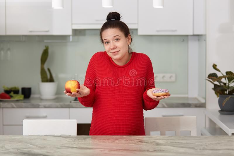 Det inomhus skottet av den unga gravida kvinnan med äpplet och den smakliga kakan i hennes händer, avgör vad för att äta, attrakt arkivfoton