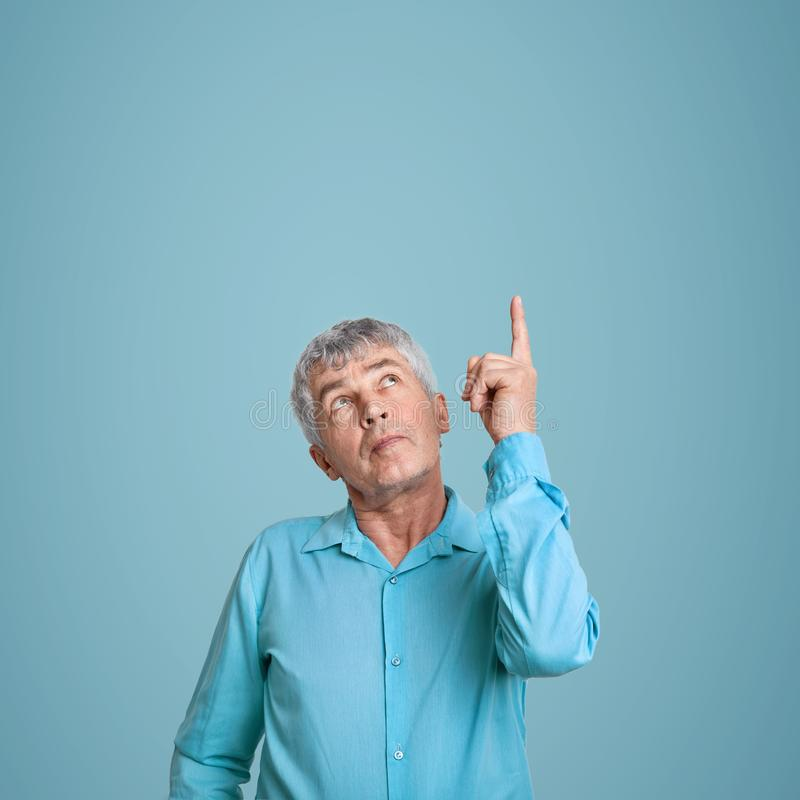 Det inomhus skottet av stiliga gråa haired manpunkter med pekfingret, bär den blåa skjortan, ställningar över tomt utrymme, visar arkivbilder