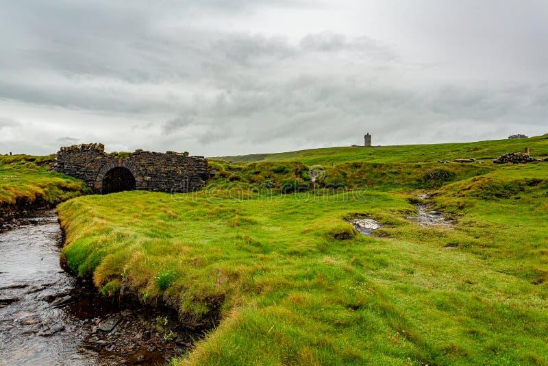 Det irländska bygdlandskapet med ett gammalt stenar bron och slotten Doonagore i bakgrunden royaltyfria bilder