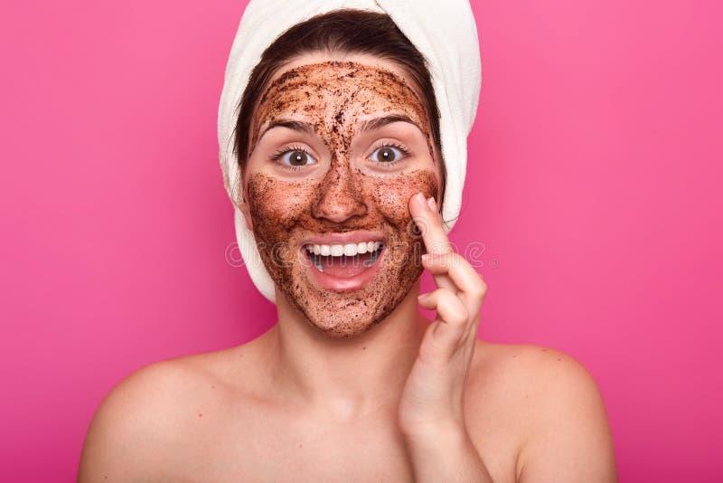 Det isolerade skottet av den förvånade kvinnan applicerar maskeringen på framsida, har lycklig ansikts- expresion, öppnar munnen  arkivbild