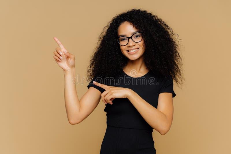 Det isolerade skottet av lyckliga afrikansk amerikankvinnapunkter upp och åt sidan, visar tomt kopieringsutrymme för din annonser arkivfoto