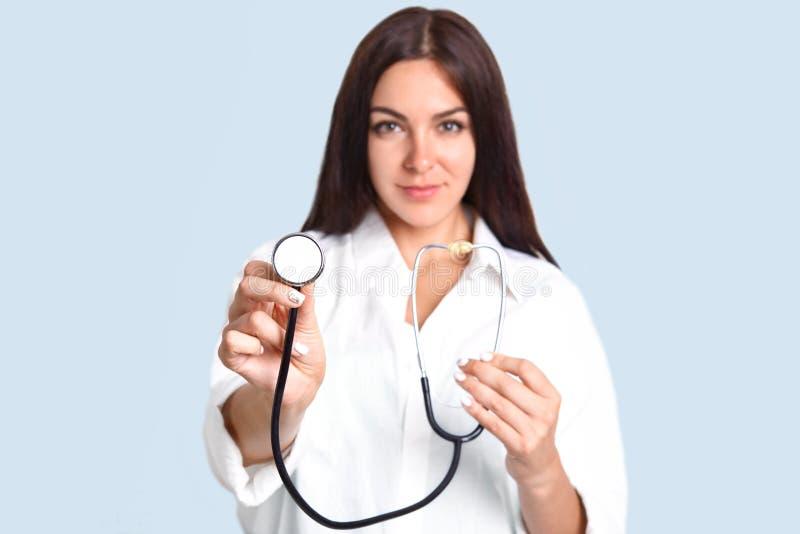 Det isolerade skottet av prett som den säkra kvinnliga doktorn annonserar hennes nya phonendoscope, ordnar till för att undersöka royaltyfria bilder