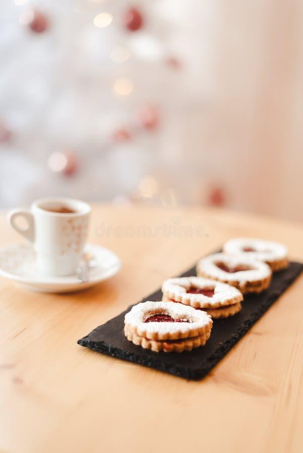 Det italienska kaffet, småcupen och kakan på bordet nära julgranen med guldbokeh arkivfoton