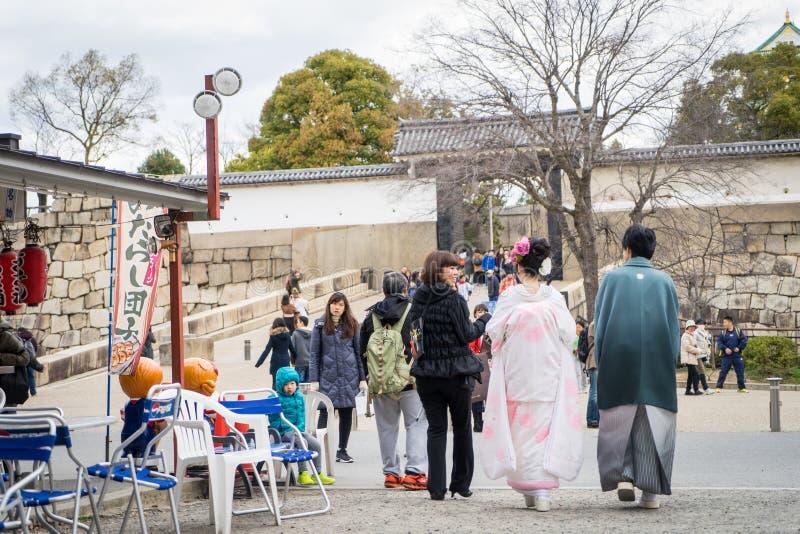 Det japanska gifta paret som går i Osaka Castle, parkerar fotografering för bildbyråer